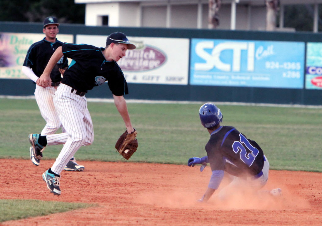 Alfredo Escalera of IMG Academy slides past the tag of Austin Sander of Coral Reef in the Premier Bracket of the Sarasota Classic on Thursday at Sarasota High. (Photo by Dennis Maffezzoli)